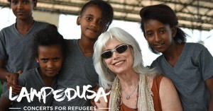 Emmylou Harris poses with young refugees at Adi Harush refugee camp in northern Ethiopia, June 8, 2016. The camp is home to refugees from Eritrea, and a significant percentage of the population are unaccompanied children. (Christian Fuchs — Jesuit Refugee Service/USA)
