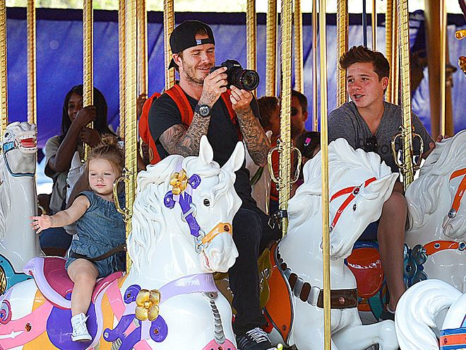 David Beckham is in full daddy mode while snapping pictures of his kids at Disneyland. Cute, cute, cute!